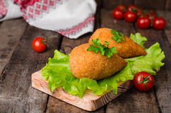 Chicken cutlets in breadcrumbs - Chicken Kiev on wood board and wooden background. Ukrainian cuisine. Selective focus Stock Photo