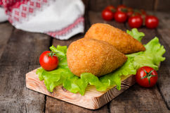 Chicken cutlets in breadcrumbs - Chicken Kiev on wood board and wooden background. Ukrainian cuisine. Selective focus Stock Image