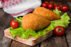 Chicken cutlets in breadcrumbs - Chicken Kiev on wood board and wooden background. Ukrainian cuisine. Selective focus Royalty Free Stock Photography