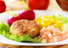 Chicken cutlets with canned corn and shrimp. Stock Photo