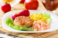 Chicken cutlets with canned corn and shrimp. Royalty Free Stock Photos