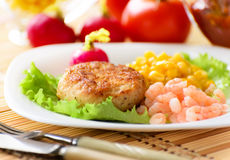 Chicken cutlets with canned corn and shrimp. Stock Photography