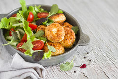 Chicken cutlets and fresh vegetable salad in a vintage pan Stock Photos