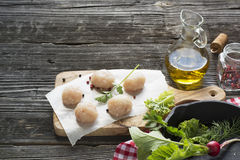 Chicken cutlets on frying pan. style rustic. selective focus. Meatballs from raw chicken meat before cooking on the board of the olive tree with fresh herbs Stock Images