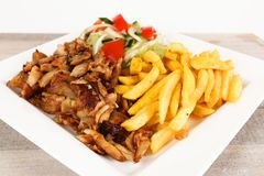 Chicken doner with fries and salad. Chicken doner on a plate with fries and salad stock photos
