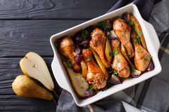 Chicken drumstick baked with honey pears and red onion close-up. Chicken drumstick baked with honey pears and red onion close-up on the table. Top view from Royalty Free Stock Images