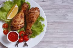 Chicken drumstick with lettuce, tomatoes and ketchup top view. Roasted chicken drumstick with lettuce, cherry tomatoes and ketchup on a white plate. top view stock image