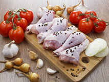 Chicken drumstick with vegetables. On wooden table Stock Image