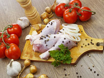 Chicken drumstick with vegetables. On wooden table Royalty Free Stock Photos
