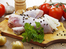 Chicken drumstick with vegetables. On wooden table Stock Images