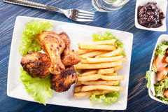 Chicken drumsticks with chips Royalty Free Stock Photo