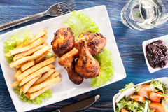 Chicken drumsticks with chips Royalty Free Stock Photography