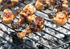 Chicken legs on the grill. Chicken drumsticks cooking on the grill stock photos