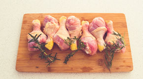 Chicken drumsticks on a cutting board with fresh rosemary and th Royalty Free Stock Image