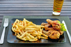 Chicken drumsticks with french fries on black plate Stock Photos