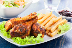 Chicken drumsticks with french fries Stock Photos