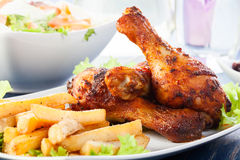 Chicken drumsticks with french fries Stock Photo