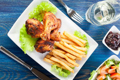 Chicken drumsticks with french fries Stock Photography