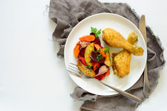 Chicken drumsticks with garnish. Chicken drumsticks with roasted vegetables garnish in a plate, view from above Royalty Free Stock Photos