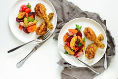 Chicken drumsticks with garnish. Chicken drumsticks with roasted vegetables garnish in two plates, view from above Royalty Free Stock Photo