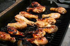 Chicken drumsticks left cooking on barbeque. Chicken drumsticks left cooking on outdoor barbeque Royalty Free Stock Image