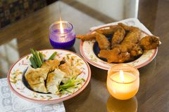 Chicken Dumpling And Chicken Wings. Chinese pan fried dumpling and chinese fried chicken wings on the table with 2 candles stock image
