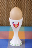 Chicken egg on the pedestal standing on the table. Chicken egg on the pedestal stand on a table covered with a tablecloth Royalty Free Stock Photography