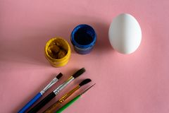 Chicken egg on pink pastel background with brushes for drawing top view royalty free stock image