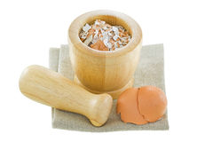 Chicken egg shells next to a wooden pestle and mortar with crush Stock Photo