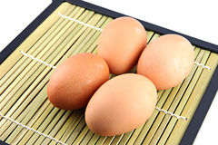 Chicken eggs on bamboo dish. Royalty Free Stock Images