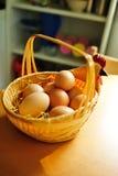 Chicken eggs in a wicker basket. Fresh chicken eggs in wicker basket on the table in the kitchen Stock Image