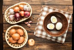 Chicken eggs in basket decorated with food ingredients on wooden. Chicken eggs in basket decorated with food ingredients on an old wooden table Royalty Free Stock Photo