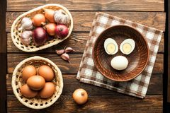 Chicken eggs in basket decorated with food ingredients on wooden. Chicken eggs in basket decorated with food ingredients on an old wooden table Royalty Free Stock Photography