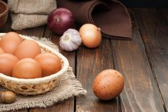 Chicken eggs in basket decorated with onions on wooden table Royalty Free Stock Photography
