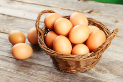 Chicken eggs in basket on grey wooden background. Royalty Free Stock Photography