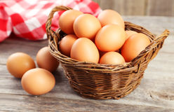 Chicken eggs in basket on grey wooden background. Stock Photography