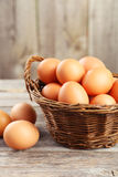 Chicken eggs in basket on grey wooden background. Stock Images
