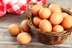Chicken eggs in basket on grey wooden background. Royalty Free Stock Photos