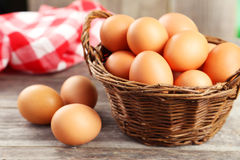 Chicken eggs in basket on grey wooden background. Royalty Free Stock Photo
