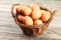 Chicken eggs in basket on the grey wooden background Royalty Free Stock Photos