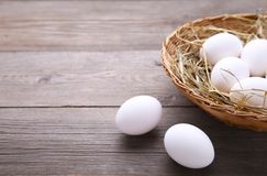 Chicken eggs in basket on grey wooden background stock photography