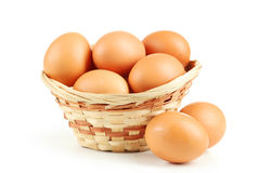 Chicken eggs in basket isolated on white. Royalty Free Stock Photo