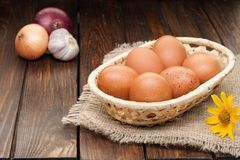Chicken eggs in basket decorated with onions on wooden table Royalty Free Stock Photo