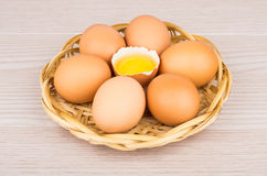 Chicken eggs in basket with one broken egg Stock Photos
