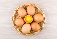 Chicken eggs in basket with one broken egg Royalty Free Stock Photo