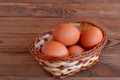 Chicken eggs in a basket. Set the raw chicken eggs. Wooden table Royalty Free Stock Image