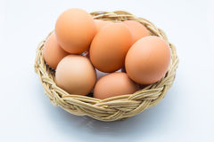 Chicken eggs in a basket on white Royalty Free Stock Photos