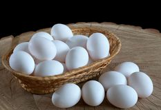 Chicken eggs in a basket on a wooden background royalty free stock images