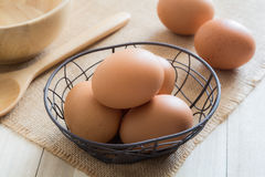 Chicken eggs in basket. On wooden background Royalty Free Stock Photography
