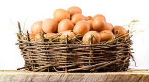 Chicken eggs in big nest isolated. Organic food royalty free stock image